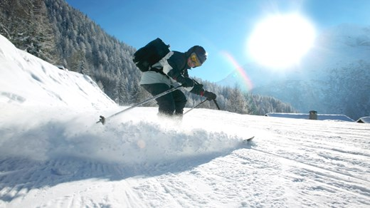 Skier coming down a slope in the French alps.
