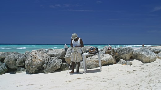 Local painter on the beach in the Caribbean.